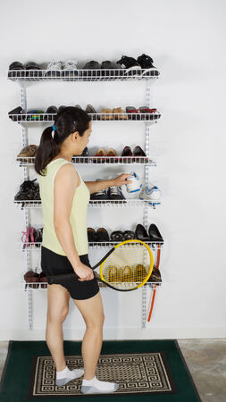 Vertical image of mature woman selecting her sports shoes from rack to play tennis