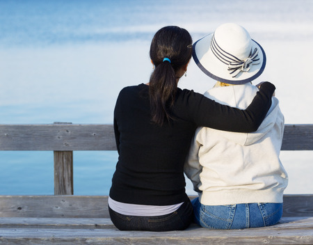 Closeup of mother and mature daughter siting on wooden bench while looking at the lake