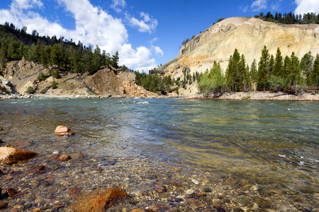 wyoming: Closeup horizontal image of Yellowstone River running through the canyon during summer day with blue sky and clouds