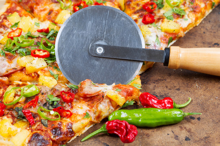 separating: Closeup view of cutting wheel separating slice of freshly baked pizza stone board Stock Photo