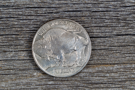 reverse: Closeup image of American Buffalo Nickel, reverse side, on rustic wood