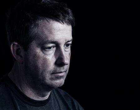 cara triste: Vista lateral cerca del hombre maduro que muestra las emociones negativas con fondo oscuro