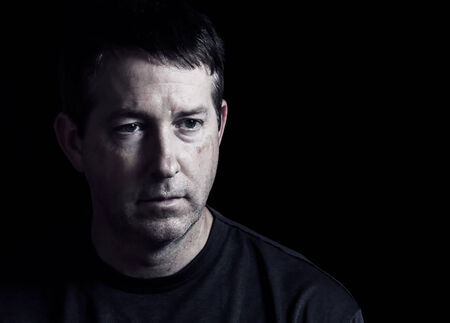 face close up: Front view close up of mature man showing negative emotions with dark background Stock Photo