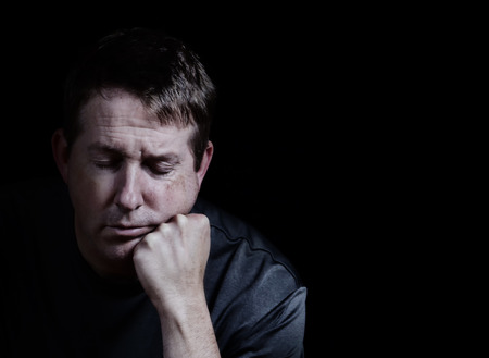Front view close up of mature man with his eyes closed and chin in hand displaying depression on black background