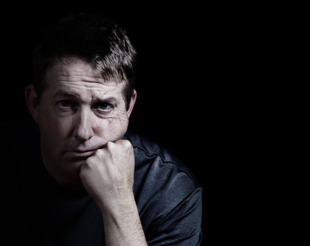 Front view close up of mature man looking forward with his chin in hand displaying depression on black background