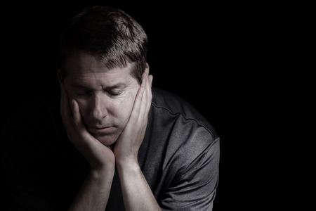 bad times: Closeup front view of mature man with head down, eyes closed and his chin in hands displaying depression on black background   Stock Photo