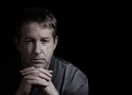 Closeup front view of mature man, looking forward, with chin resting in folded hands on dark background  Stockfoto