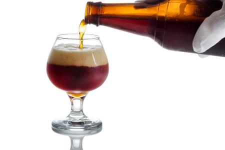 schwarzbier: Behandschuhten Hand Gie�en dunkles Bier in Glas Becher auf wei� mit Reflexion