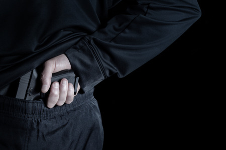 undercover: Closeup back view of male hand pulling pistol out on dark background
