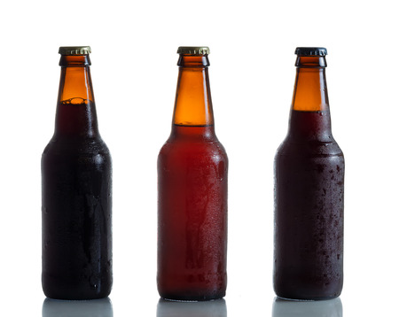 dark brown: Cold unopened dark and amber beer bottles on white with reflection