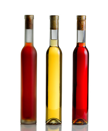 unopened: Vertical image of three unopened wine bottles on white with reflection Stock Photo