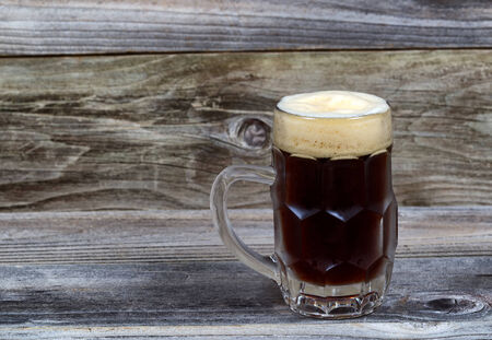 stein: Horizontal image of a glass stein filled with dark draft stout beer on rustic wood Stock Photo