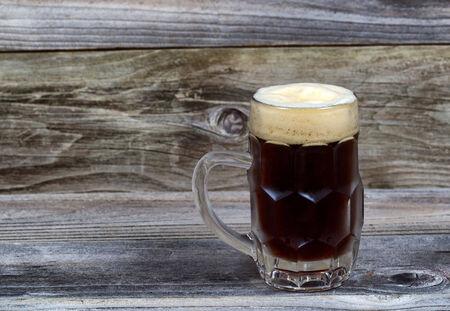 cerveza negra: Imagen horizontal de un vaso stein lleno de cerveza oscura proyecto valiente en la madera rústica Foto de archivo