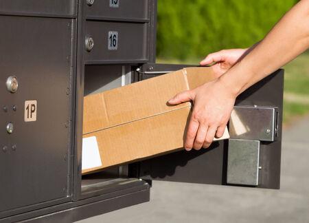 buzon: Imagen horizontal de las manos femeninas que toman gran paquete de buz�n de correo postal con la hierba verde y la acera en el fondo Foto de archivo
