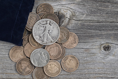 Close up view of a bag of United States vintage coins spilling out onto rustic wood 스톡 콘텐츠