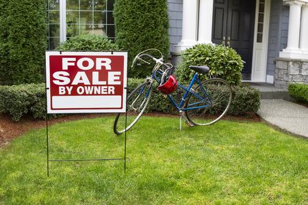 クローズ アップ ビューと現代郊外の家の販売不動産の看板の前でヤードし自転車し、バック グラウンドで家