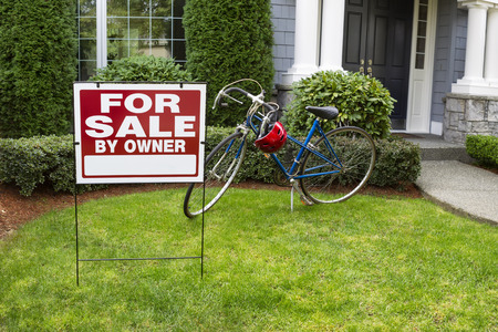 house sale: Closeup view of Modern Suburban Home with for Sale Real Estate Sign in front yard and bicycle and house in background