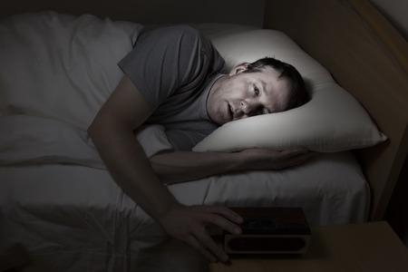insomnio: Hombre maduro, con los ojos bien abiertos con la mano en el despertador, no puede dormir por la noche de insomnio