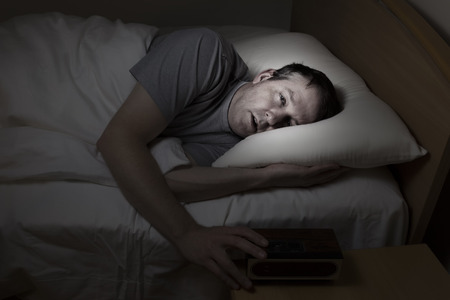awaken: Mature man, eyes wide open with hand on alarm clock, cannot sleep at night from insomnia