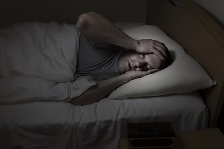 sleep: Mature man, eyes wide open with both hands on his forehead, cannot sleep at night from insomnia