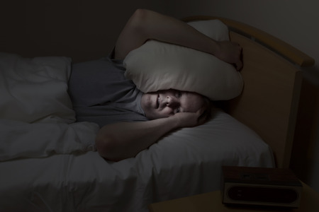Mature man, pillow over head with eyes wide open, cannot sleep at night from insomnia photo