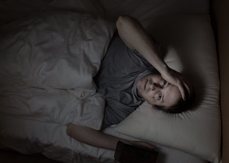 lying on bed: Top view image of mature man, looking forward, having trouble sleeping from insomnia