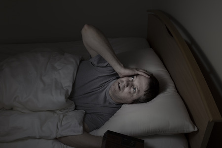 Mature man, looking up at ceiling, having trouble falling asleep at night from insomnia photo