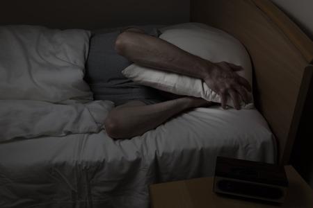 Ltere Menschen, mit Kissen bedeckt das ganze Gesicht, kann nachts nicht unter Schlaflosigkeit schlafen Standard-Bild - 32549447