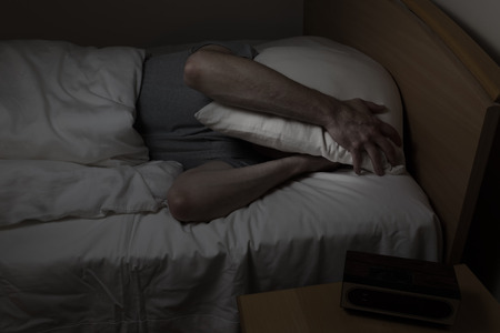 Mature man, with pillow covering entire face, cannot sleep at night from insomnia Stock Photo