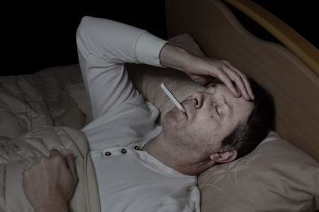 Horizontal image of mature man, with high fever, lying down in bed testing his temperature Stock Photo