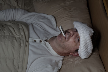 caucasian fever: Horizontal image of mature man, with wet towel on forehead, lying down in bed testing his temperature
