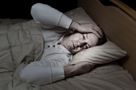 Horizontal image of sick mature man, holding his head, while in bed Stock Photo