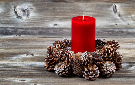 Bright red candle inside of real pine cone wreath for the Christmas season on rustic wooden boards photo
