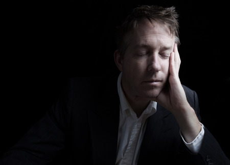 over worked: Portrait of businessman closing eyes while working late at night on black background with copy space Stock Photo
