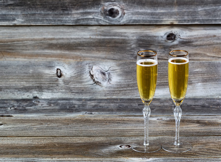 Golden champagne in elegant glasses on rustic wood photo