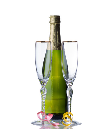 Empty tall elegant drinking glasses with unopened bottle of sparkling wine isolated over white background with reflection and party ribbons