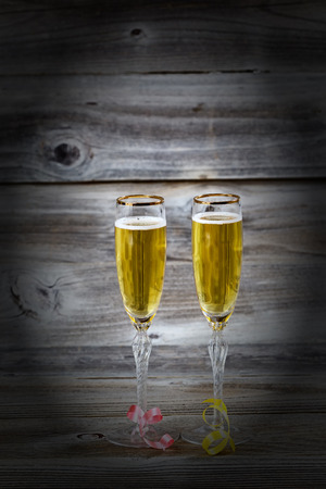 Vertical image of Golden champagne in elegant glasses on rustic wood with vignette photo