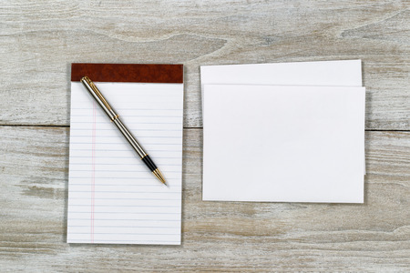 letter envelopes: Top view of business envelope and writing pen with notepad on rustic white wooden desktop