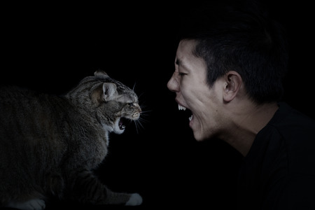 Close up of a Cat and Man showing anger towards each other on black background with light on faces