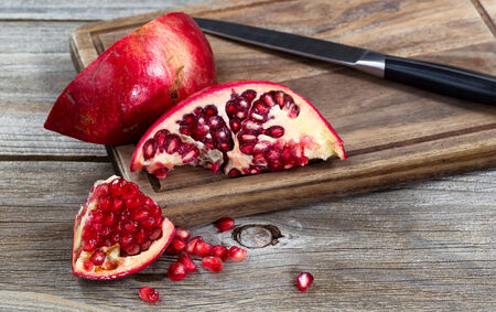 Close up of juicy ripe pomegranates with knife on vintage wood server