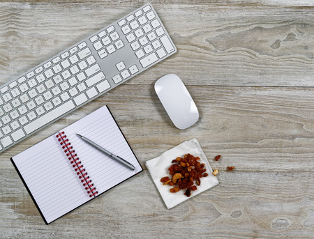 Top view of business office consisting of computer keyboard, notepad, pen, and snack food on rustic white wooden desktop photo