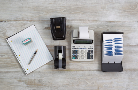 note pad and pen: Top view of office desktop with address book, calculator, tape dispenser, note pad, pen, and hole puncher