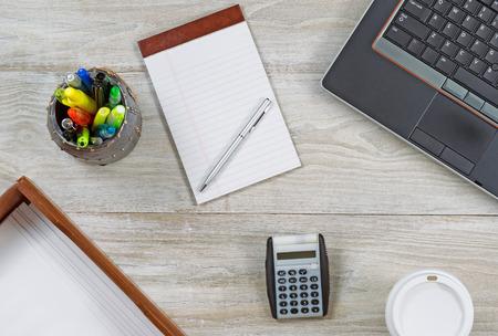 articulos oficina: Tiro superior ángulo de visión de escritorio de madera oficina en casa con varios artículos, incluyendo: ordenador portátil, teclado, bandeja de entrada, sobres de café taza de papel, bloc de notas, bolígrafo, lápiz y taza de titular pluma y calculadora.