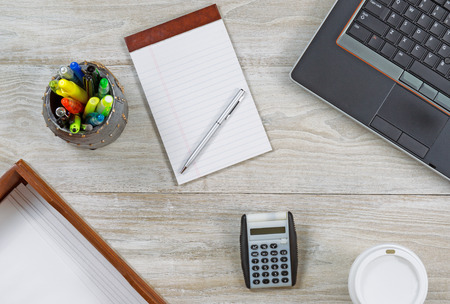note pad and pen: Top view angle shot of home office wooden desktop with various items including: laptop, keyboard, inbox, envelopes, coffee paper cup, note pad, pen, pencil and pen cup holder, and calculator.