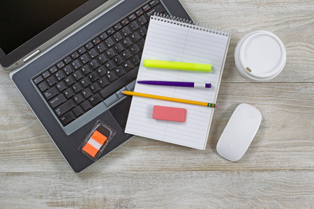 top angle: Top view angle shot of home office wooden desktop with various items including: laptop, coffee paper cup, notepad, pen, pencil, eraser, marker, and mouse. Stock Photo