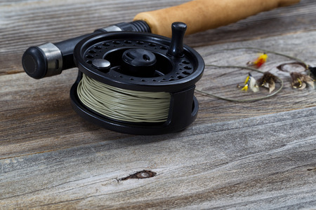 Close up of fly reel, focus on front bottom of reel, with partial cork handled pole and flies blurred out on rustic wooden boards photo