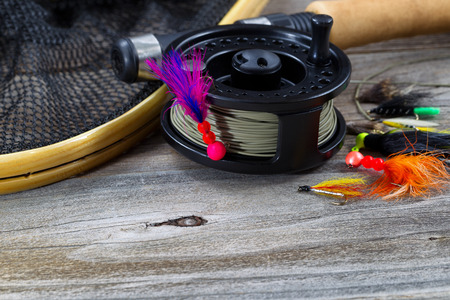 Close up of fly reel, focus on front of reel, with fly jig hanging from spool. Partial cork handled pole, net and flies blurred out on rustic wooden boards Archivio Fotografico