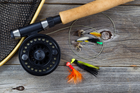 fishing pole: Close up top view of a fishing fly reel, with line, landing net and assorted flies, and partial cork handled pole on rustic wooden boards Stock Photo