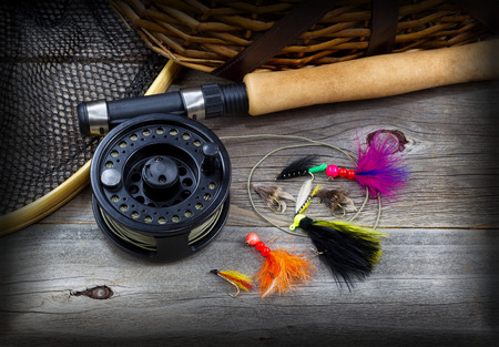 Close up top view of  fishing fly reel, landing net, creel and assorted flies, partial cork handled pole on rustic wooden boards with vignette border