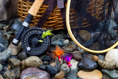 Closeup of fishing fly reel, landing net, creel and assorted flies on wet river bed stones Stock Photo